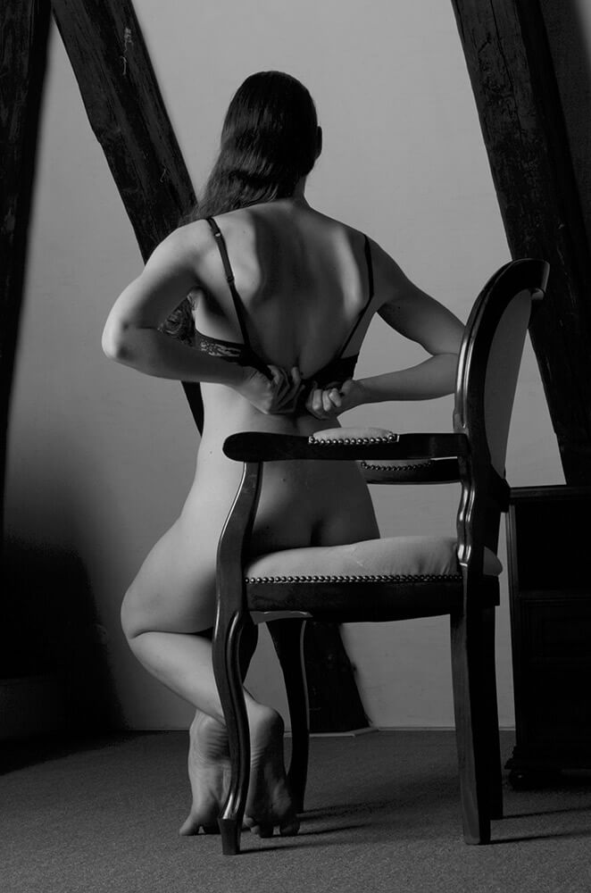 black and white boudoir photo of a woman sitting in lingerie on a chair in the room