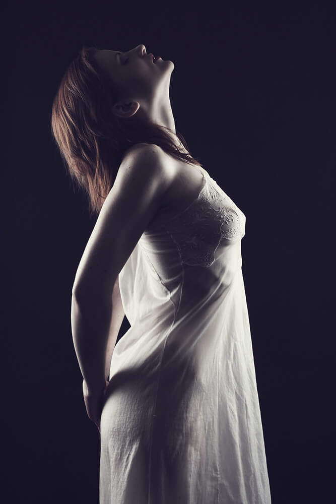 boudoir photo of a woman in a negligee on a dark background