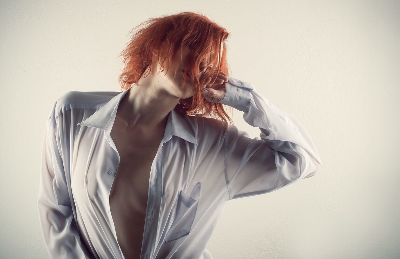 boudoir photo of a woman in a men's shirt on a light background