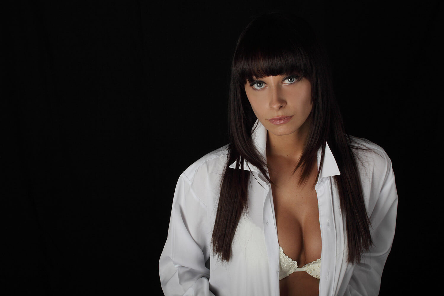 boudoir photo of a woman in lingerie and in a men's shirt on a black background