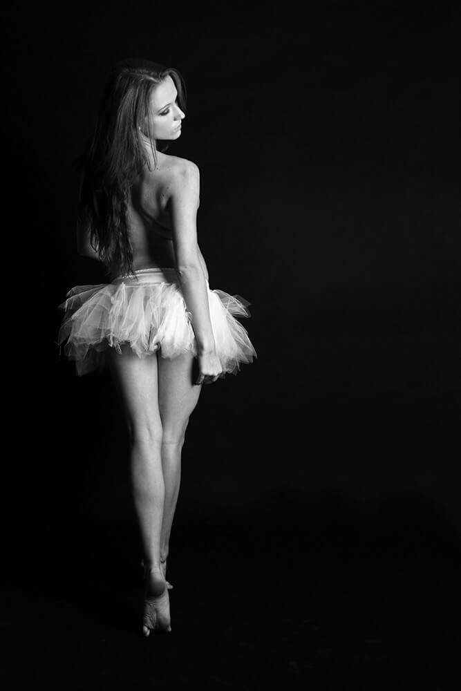 black and white boudoir photo of a woman in a ballet skirt