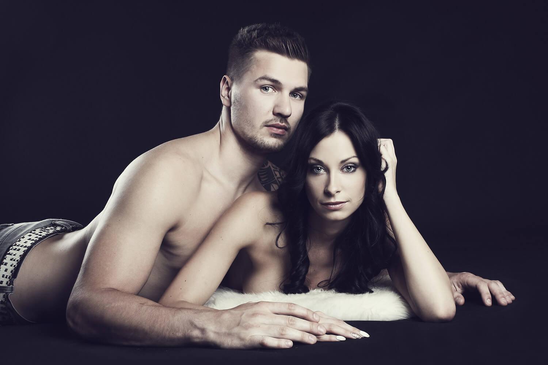 párová fotografie muže a ženy ležících na kožešině na černém pozadí