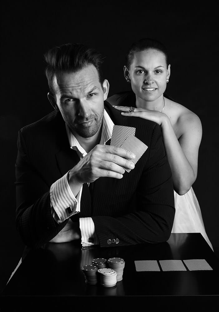 couple photo of a man in a suit and a woman in a dress and with poker cards and chips