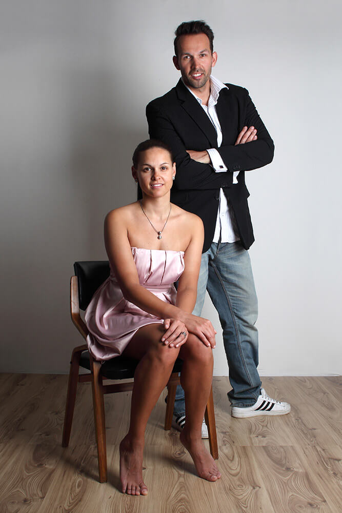 pair photo of a standing man in a jacket and a sitting woman in a dress