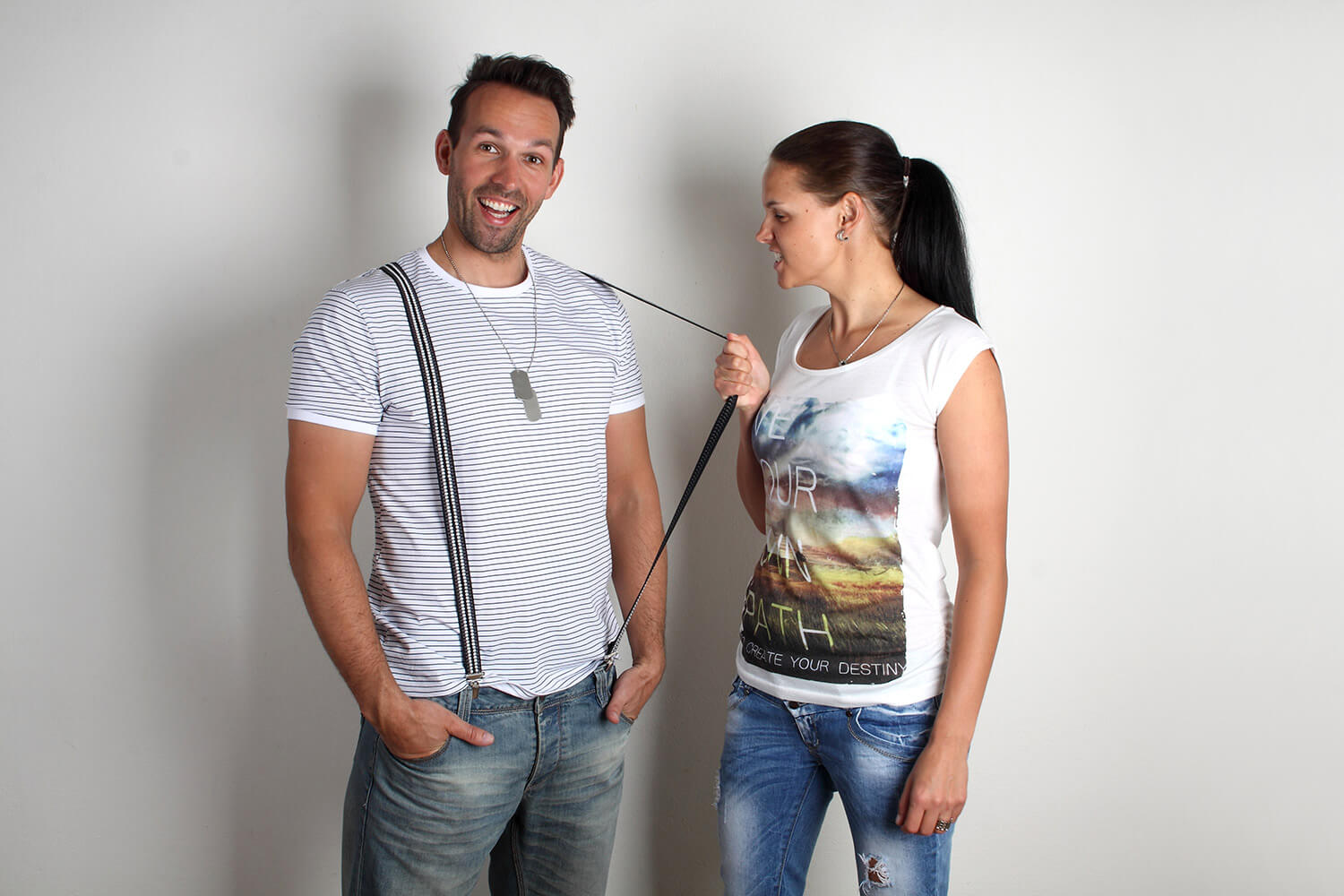 couple photo of a woman and a man with suspenders on a light background