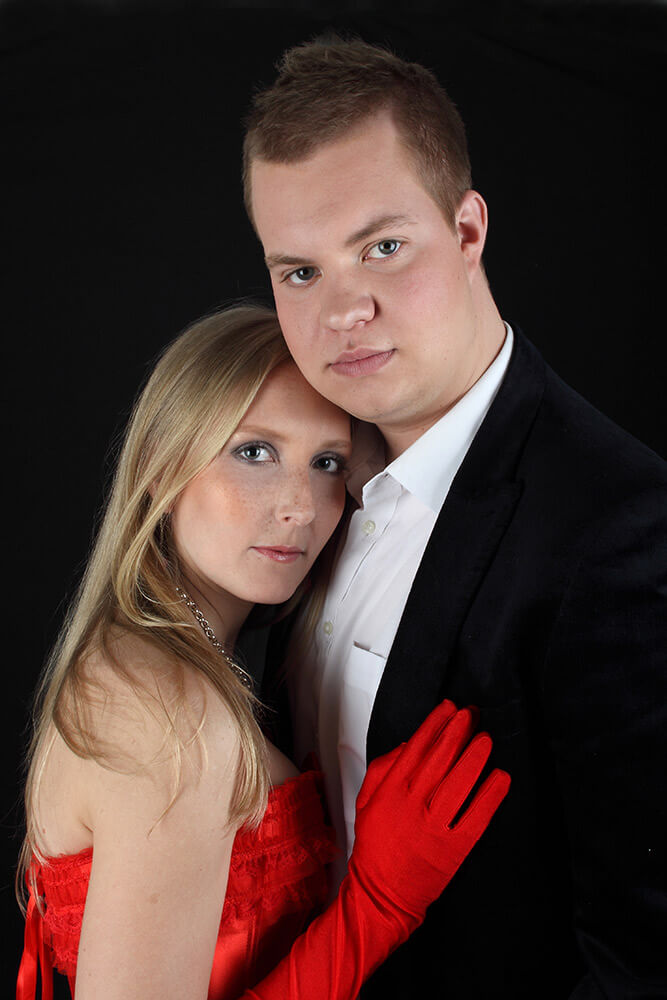 couple photo of a woman in a red dress and a man in a jacket
