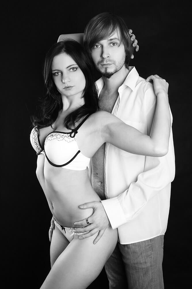 black and white couple photo of a woman in lingerie and a man in a shirt on a dark background