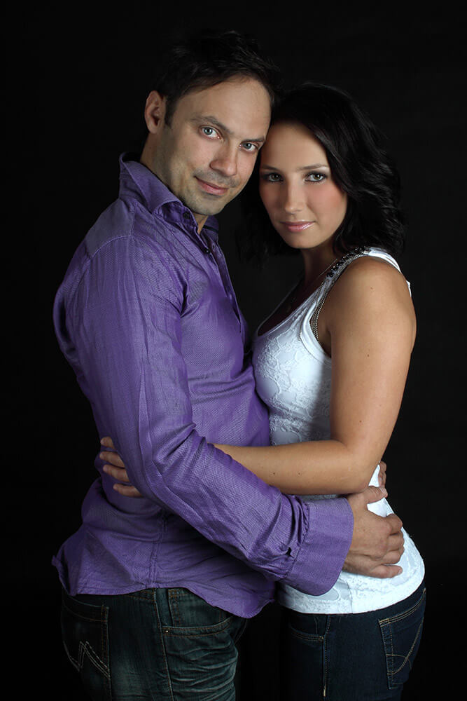 couple photo of a woman and a man in a purple shirt on a dark background