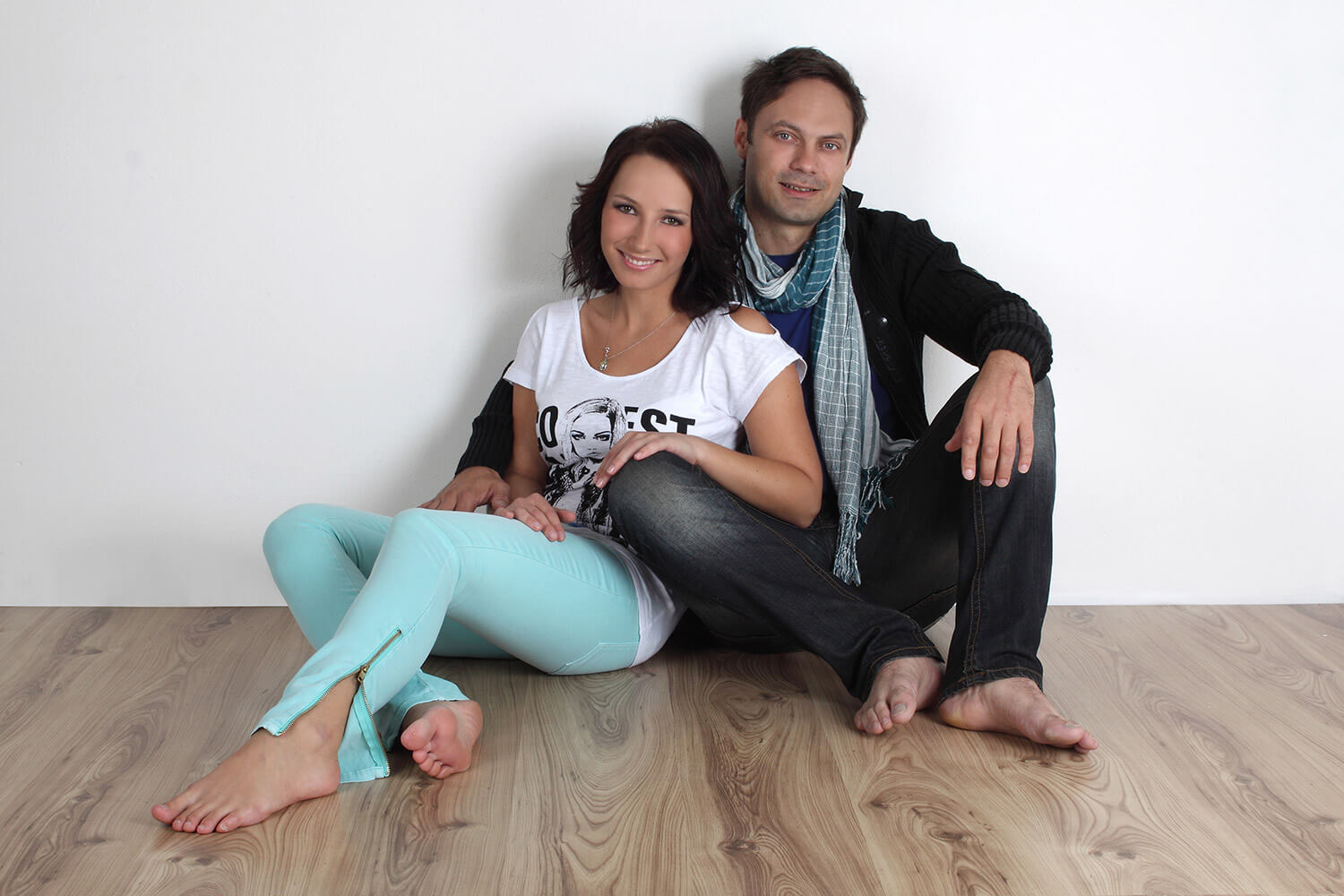 couple photo of a woman and a man sitting on the floor on a light background