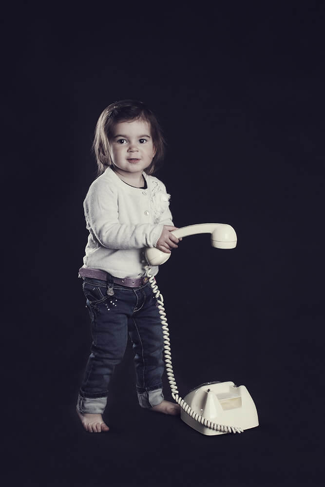family photo of a little girl with an old phone on a dark background