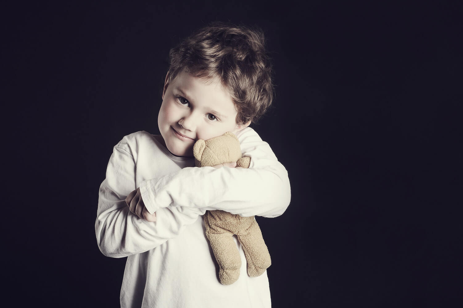 Family photo of a boy with a teddy bear on a dark background