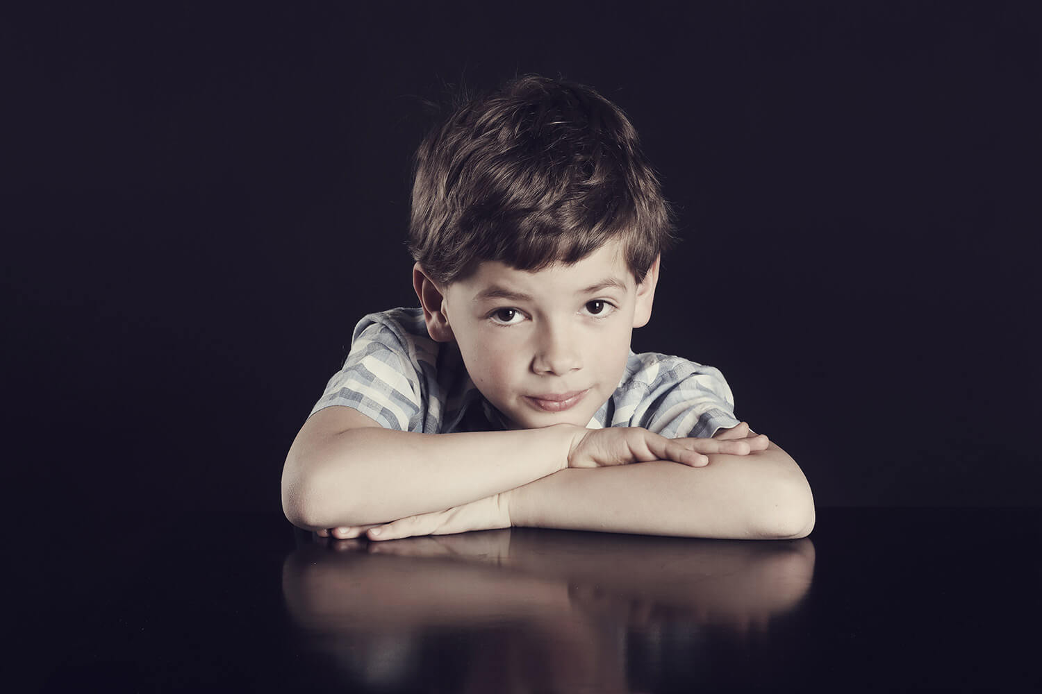 Family photo of a boy with his arms folded under his chin on a dark background