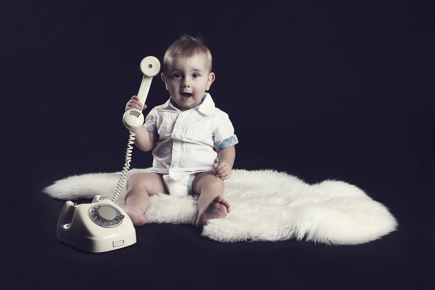 Family photo of a toddler on a fur and with an old phone on a dark background