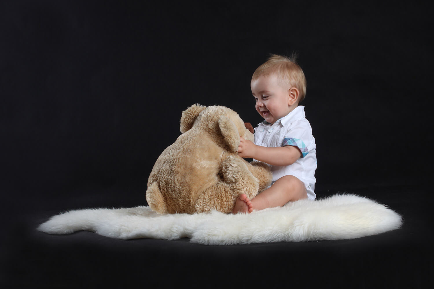 family photo of a toddler on a fur with a bear on a dark background