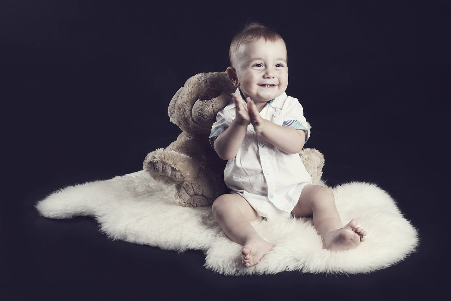 family photo of a toddler on a fur with a teddy bear behind his back on a dark background