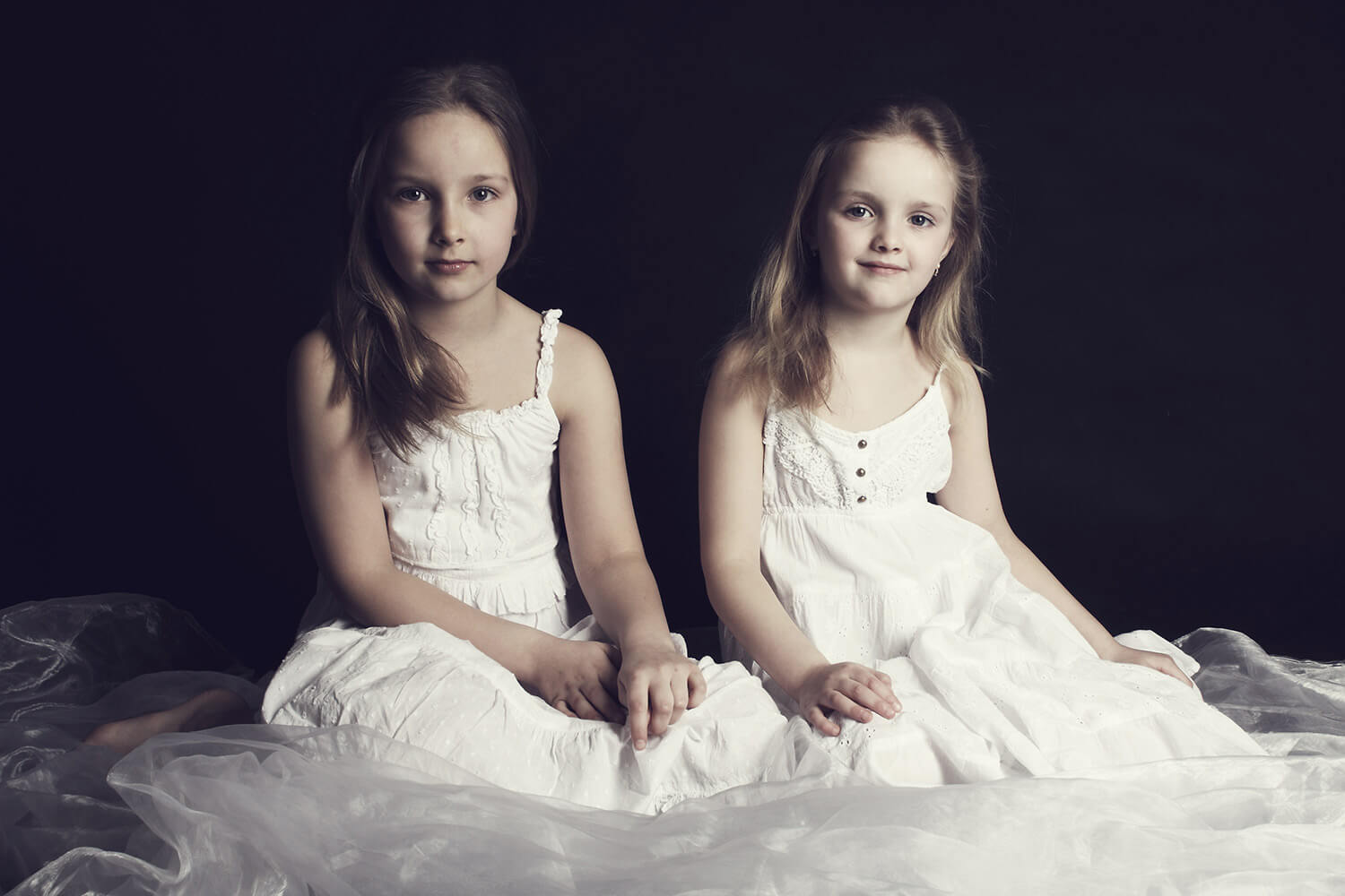 family photo of two sisters in white dresses on a dark background