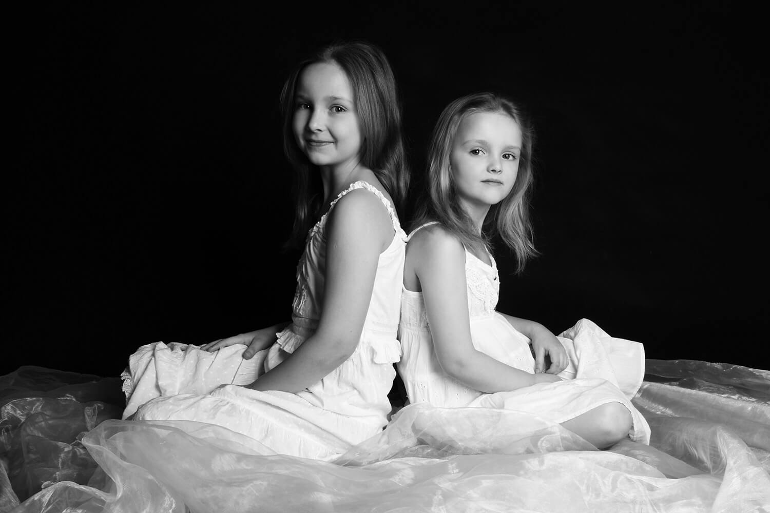 black and white family photo of two sisters in white dresses on a dark background