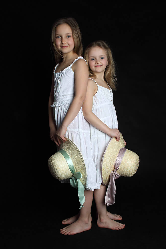 family photo of two sisters in white dresses and with hats on a dark background