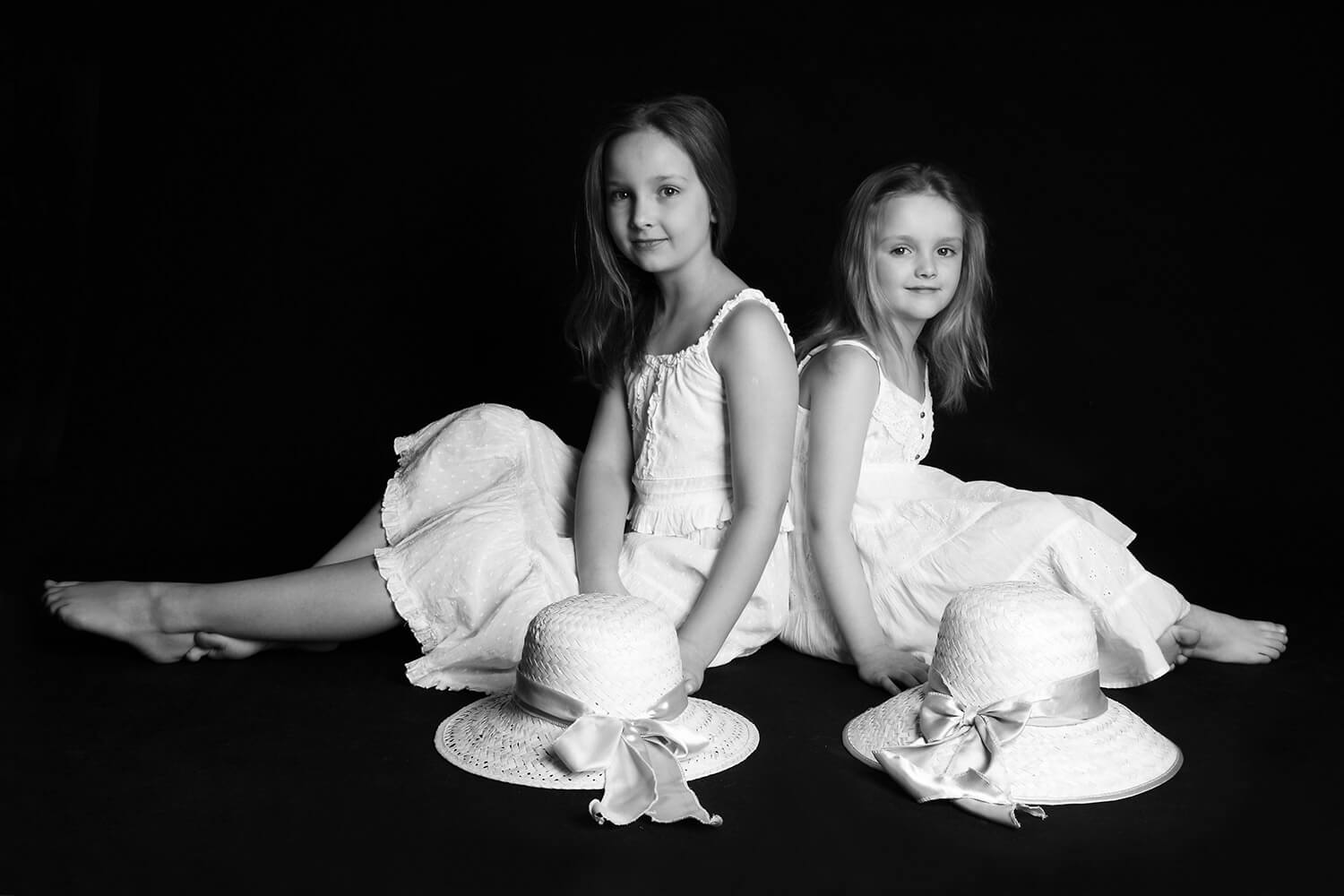 black and white family photo of two sisters in white dresses and with hats on a dark background