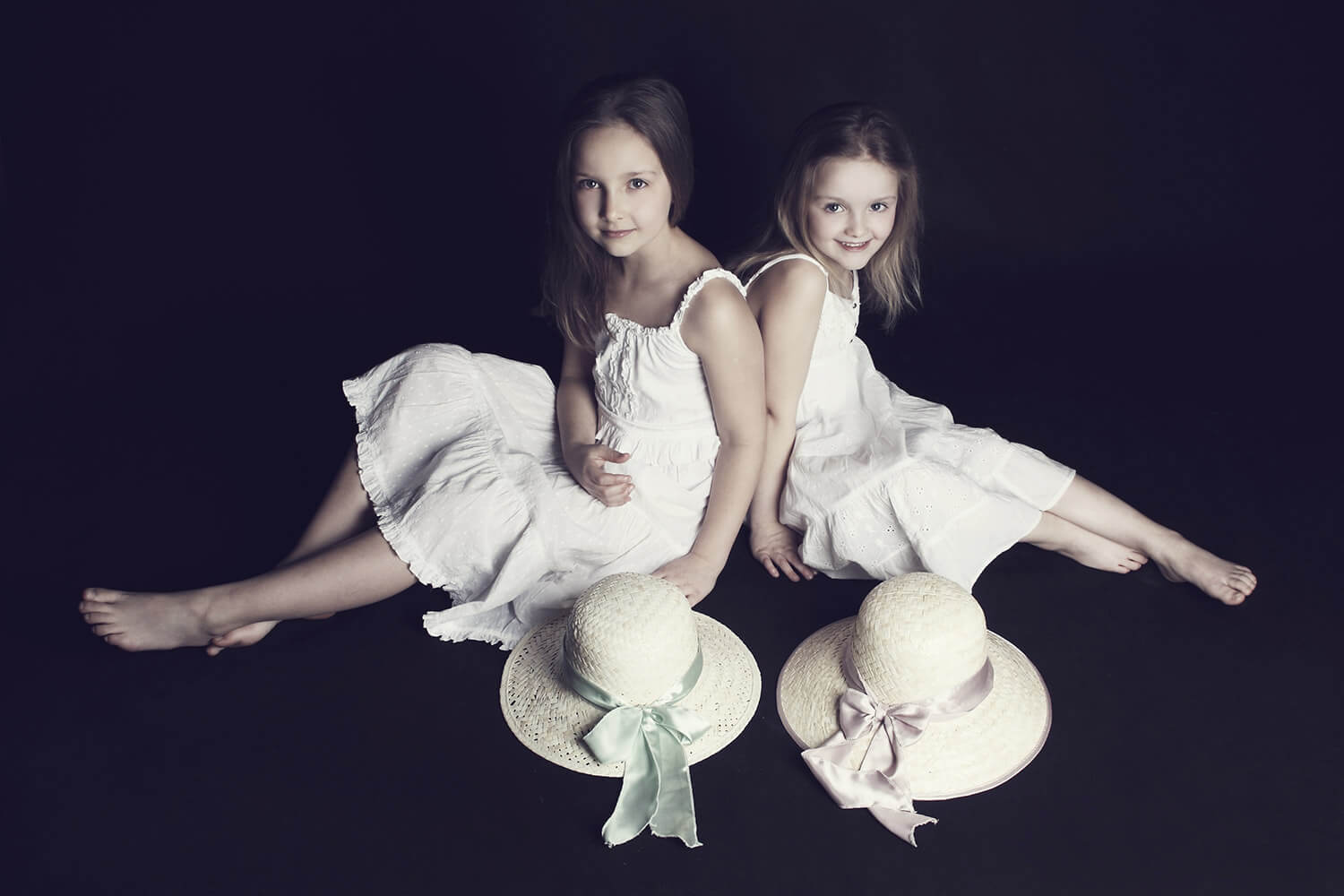 family photo of two sisters sitting in white dresses and with hats on a dark background
