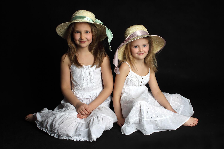 rodinná fotografie dvou sester sedících v bílých šatech a s klobouky na hlavách