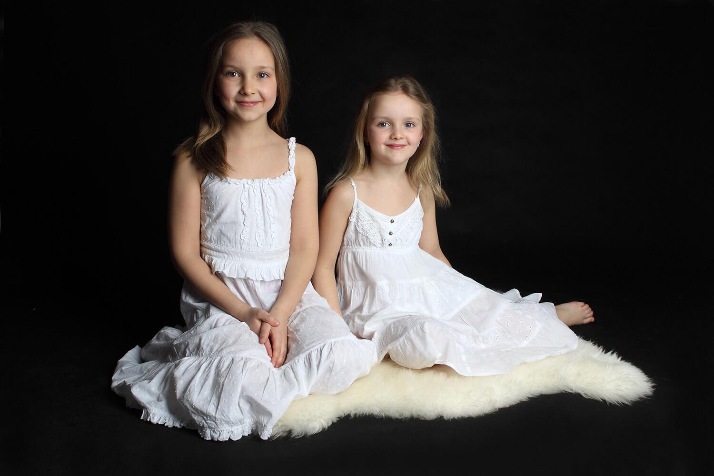 rodinná fotografie dvou sester v bílých šatech sedících na bílé kožešině