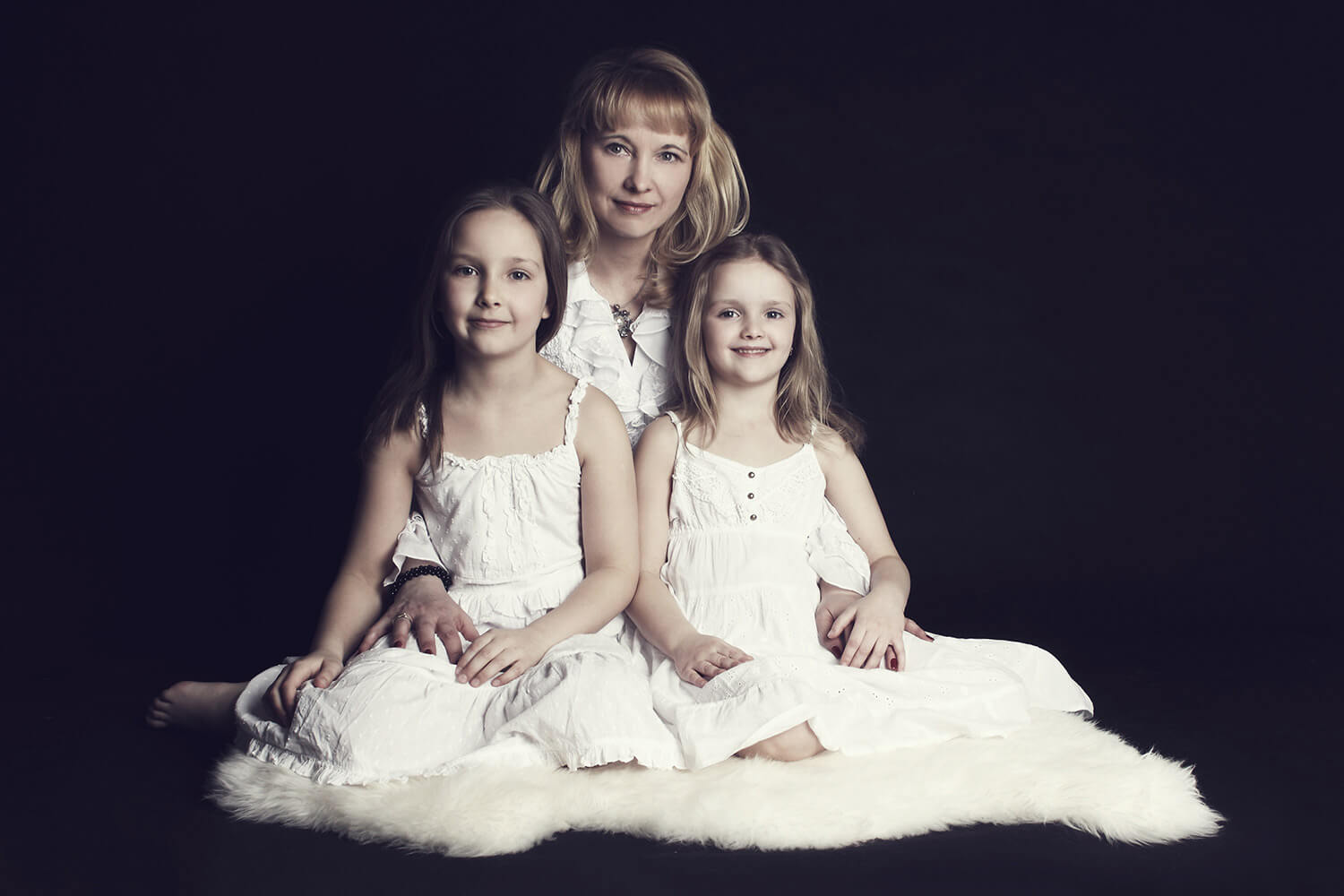 family photo of two sisters with their mom sitting on a white fur