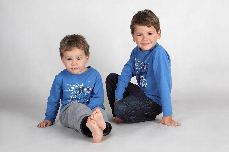 rodinná fotografie dvou bratrů s modrými tričky na světlém pozadí