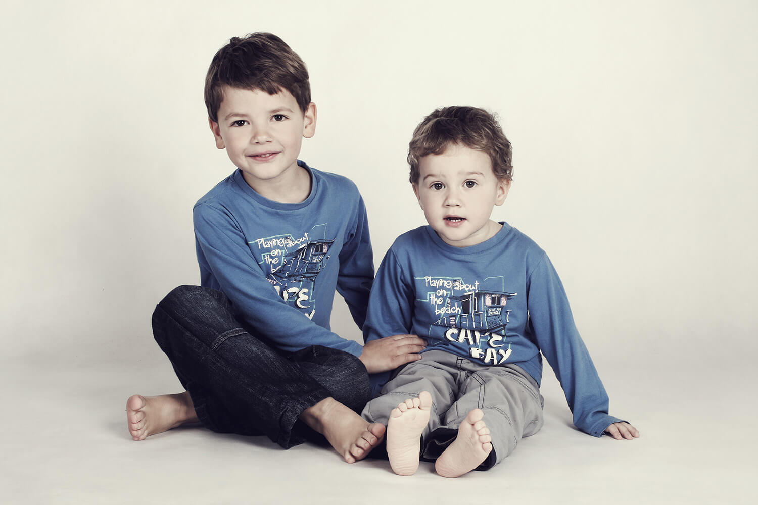 family photo of two sitting brothers with blue T-shirts on a light background