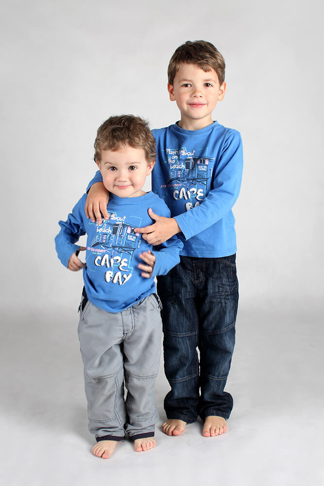 family photo of two standing brothers with blue t-shirts on a light background