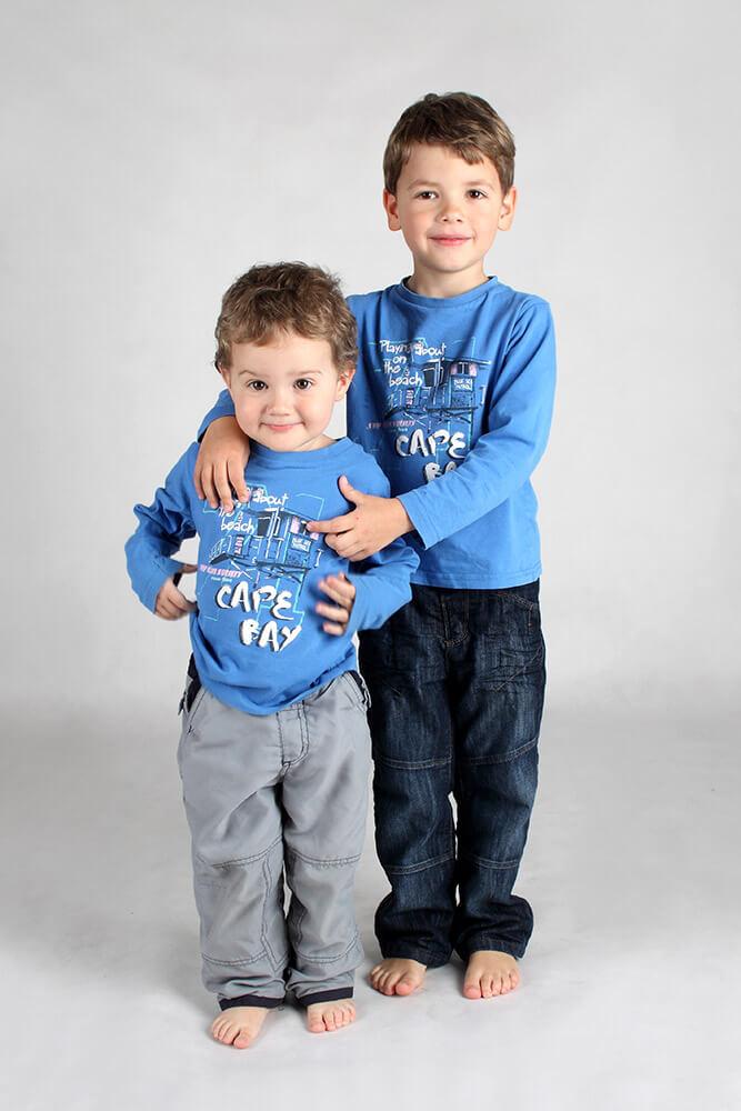 rodinná fotografie dvou stojících bratrů s modrými tričky na světlém pozadí