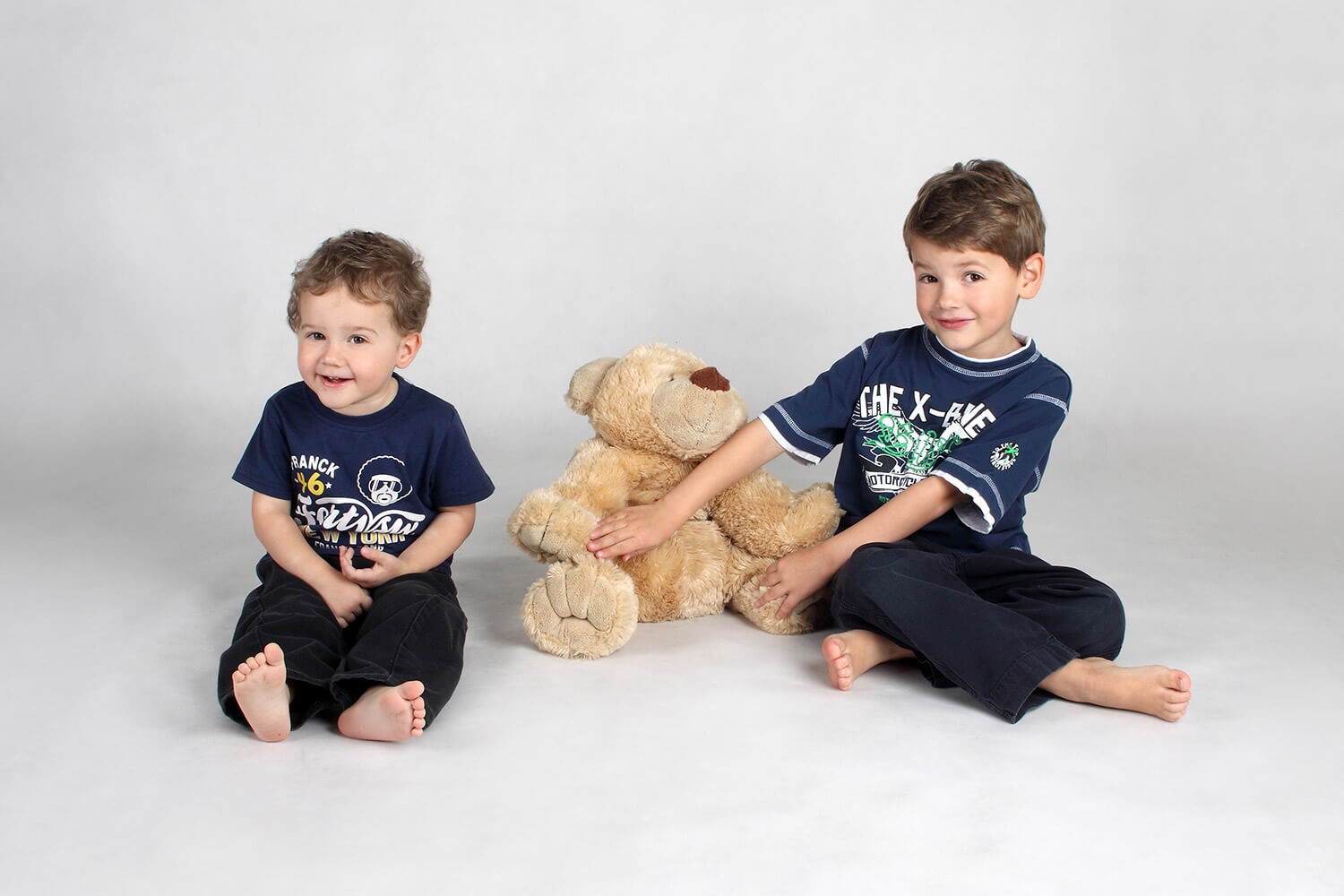 family photo of two brothers and a teddy bear on a light background