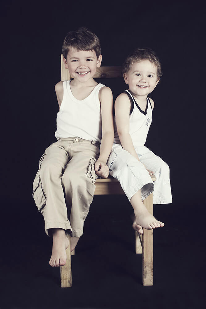family photo of two brothers sitting on one chair on a dark background