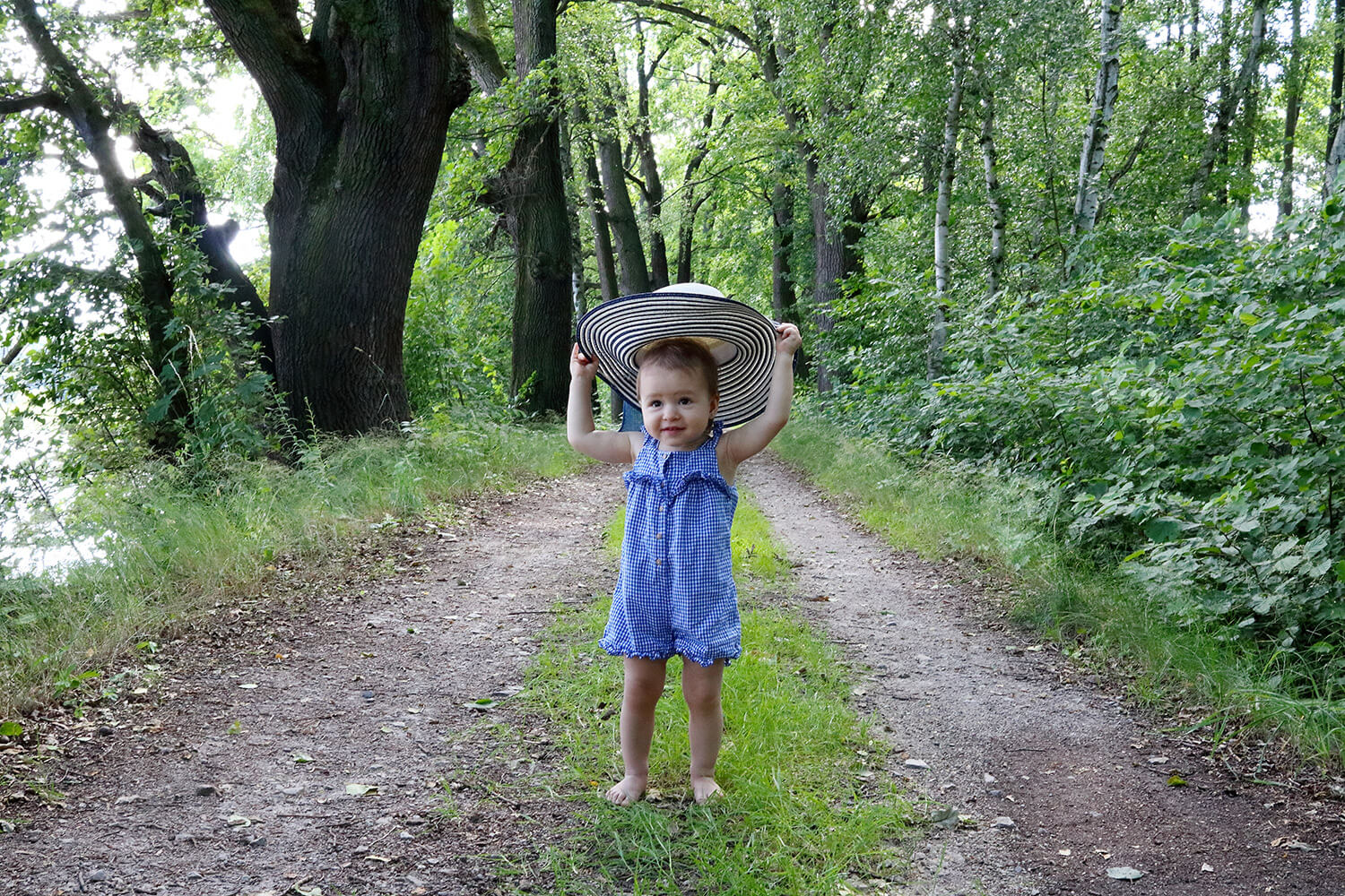 family photo of a little girl with a big hat in nature