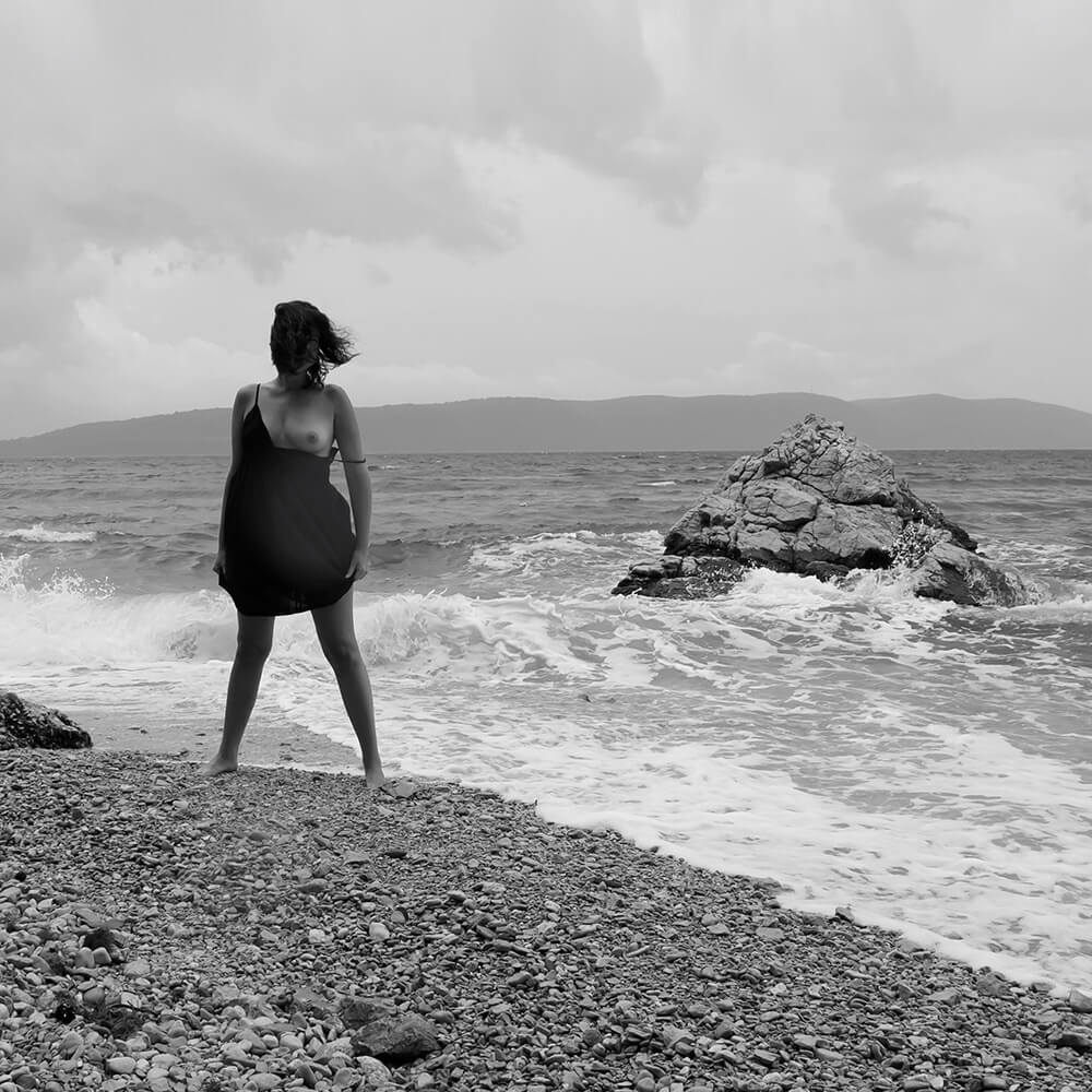 black and white fine art nude of a woman standing on a pebble beach by the stormy sea