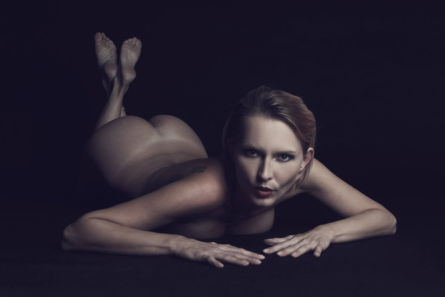 fine art nude of a woman lying on a dark background