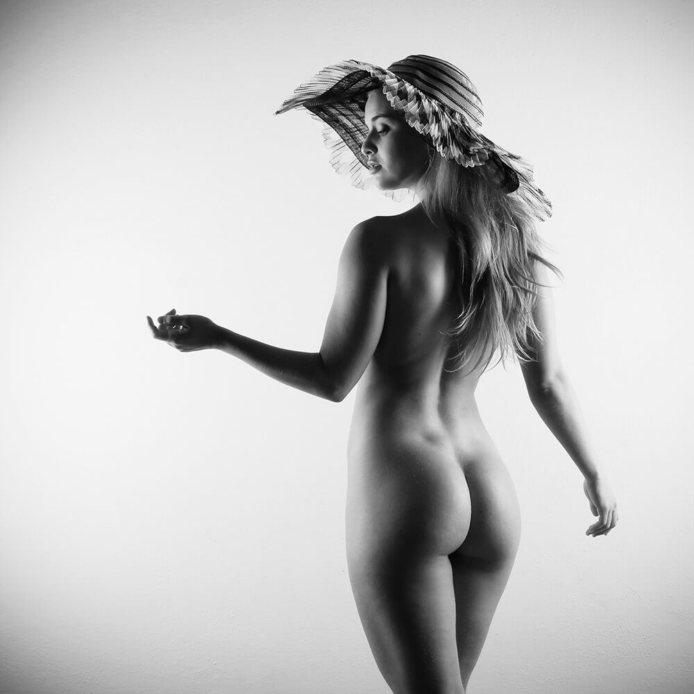 black and white fine art nude of a woman wearing a hat on a light background