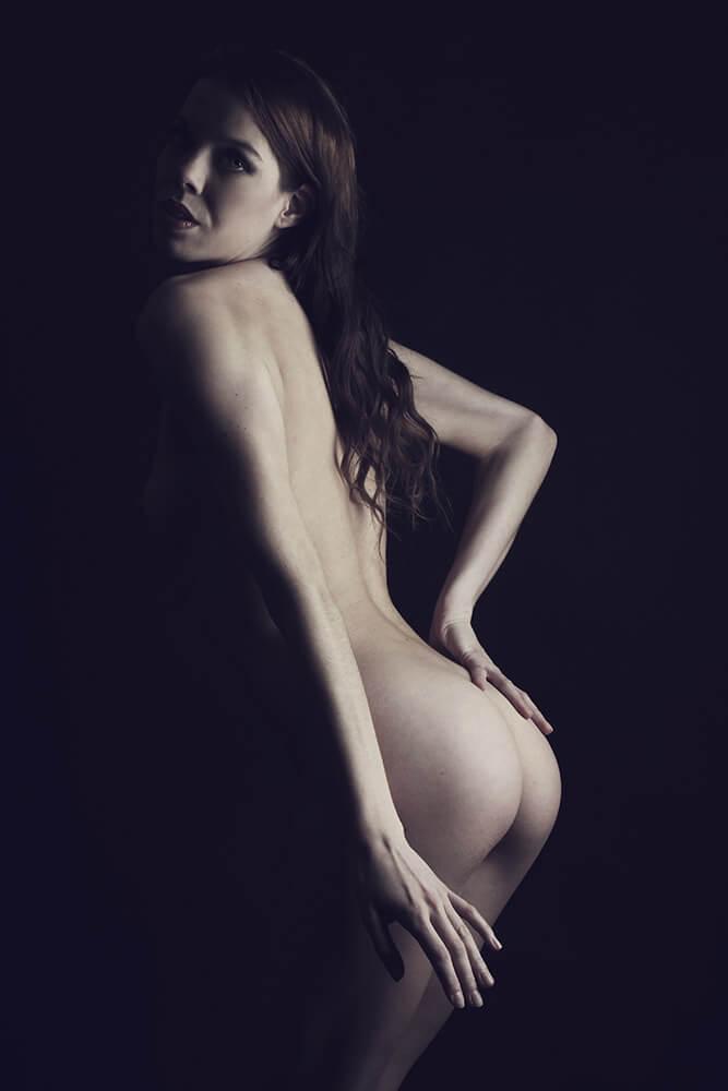 stojící ženský umělecký akt na tmavém pozadí