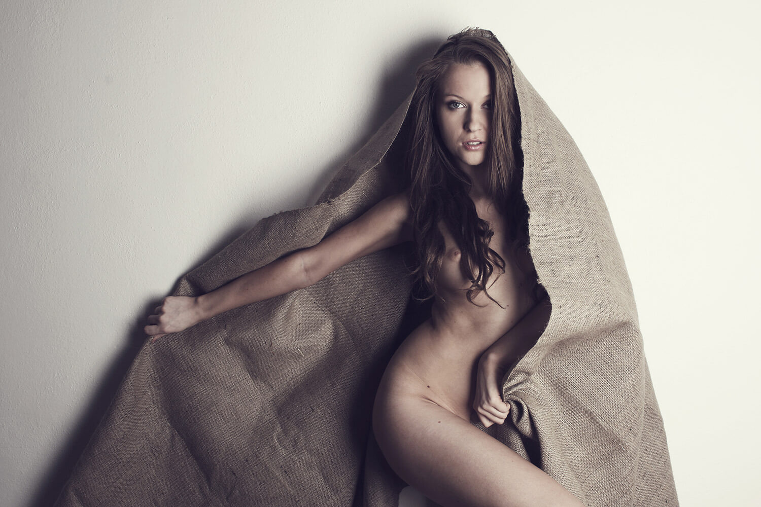 fine art nude of a woman with brown cloth on a white background