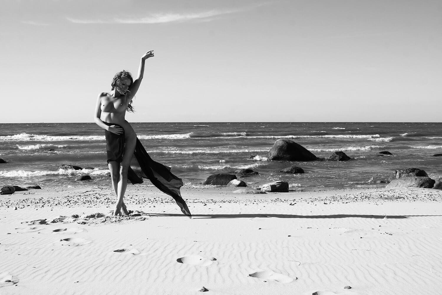 black and white fine art nude of a woman with dark fabric on the beach