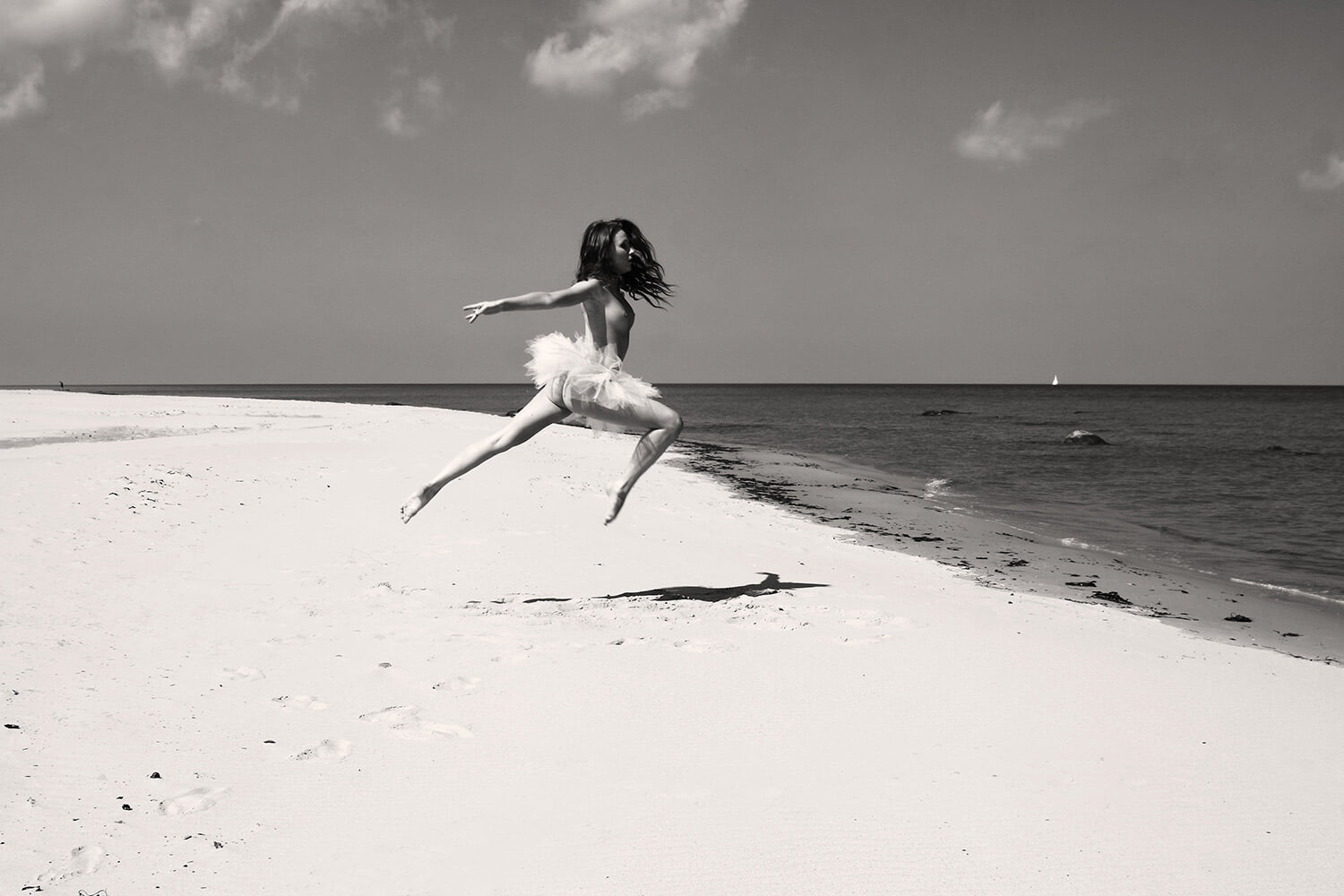 black and white fine art nude of a woman with ballet skirt on the beach