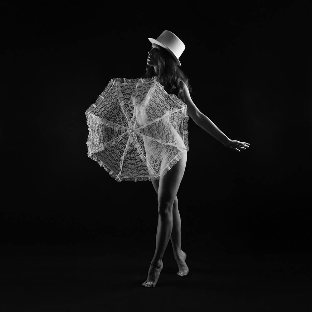 black and white fine art nude of a woman wearing a hat and a lace umbrella on a dark background