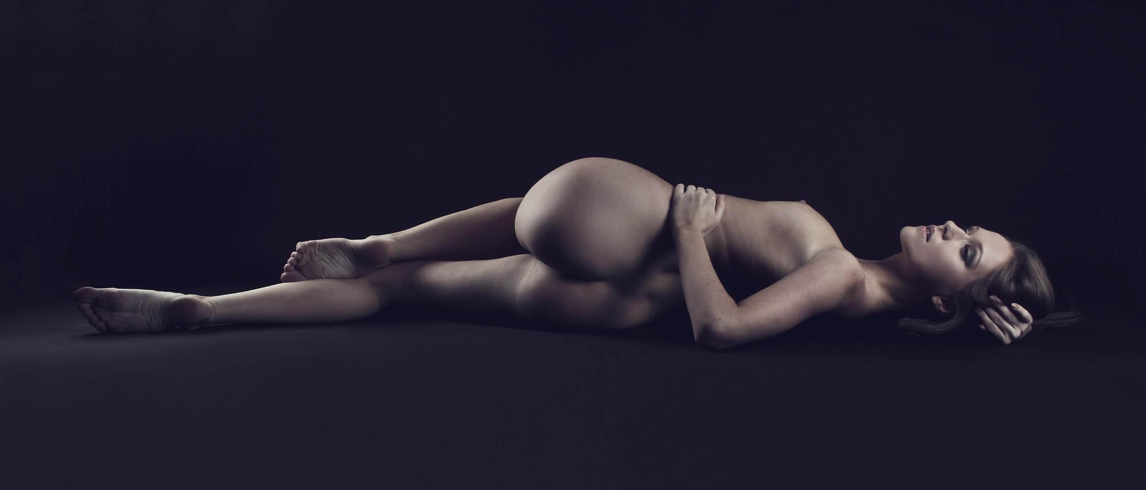 ležící ženský umělecký akt na tmavém pozadí