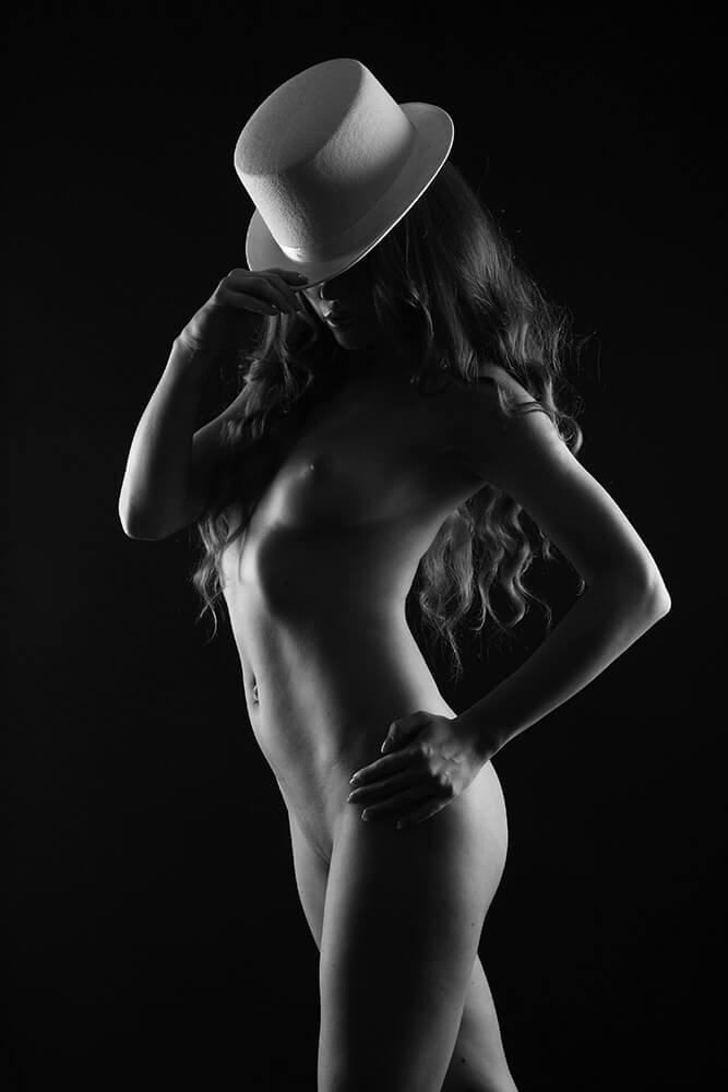 black and white fine art nude of a woman with a white hat on a dark background