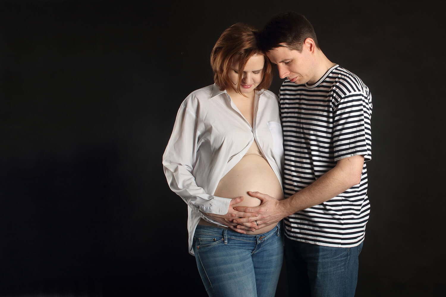 maternity photo of a couple holding belly, on a black background