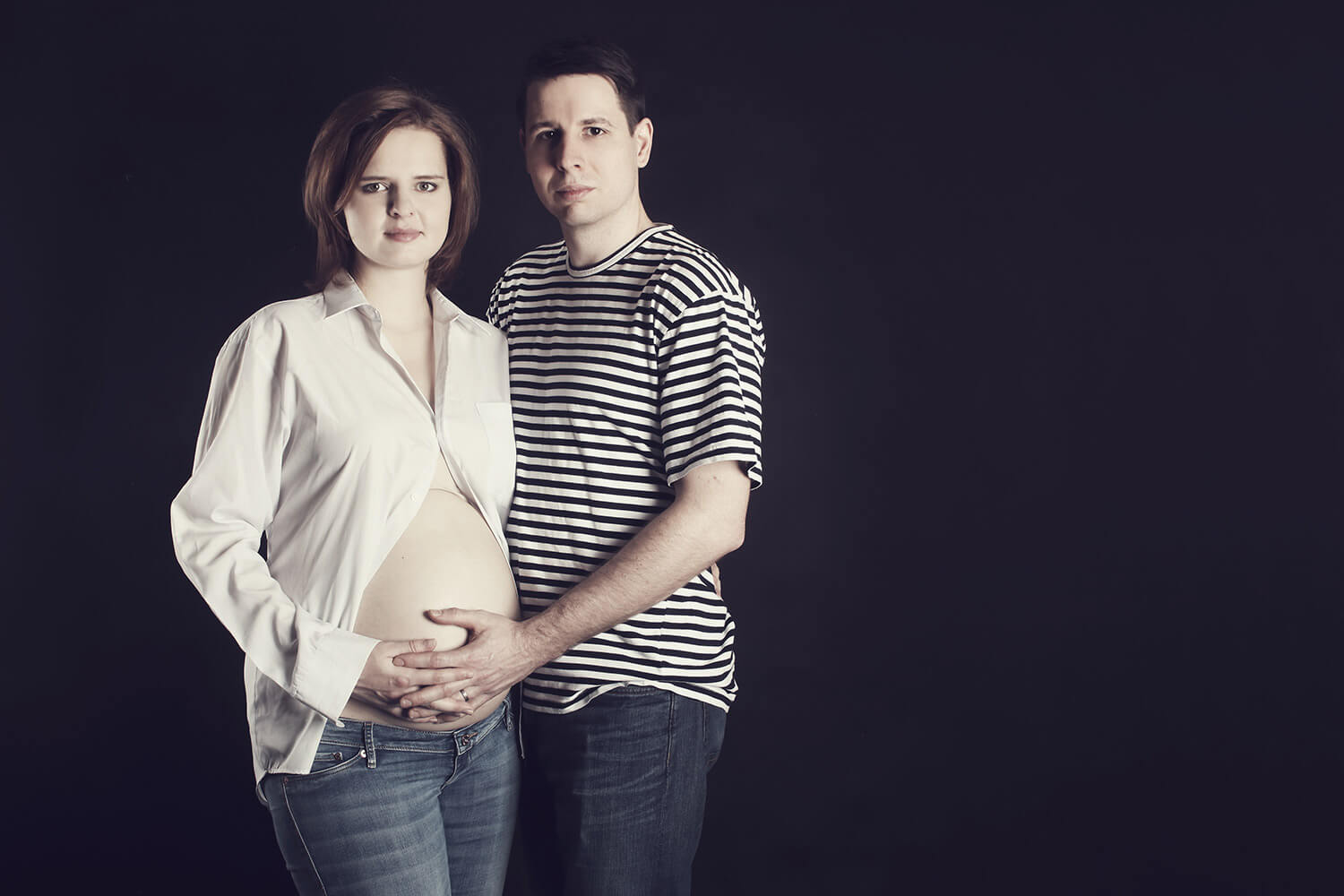 maternity photo of a couple holding belly, toned in brown