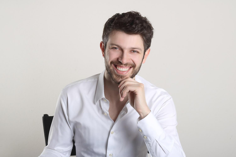 mužský business portrét v bílé košili a rukou pod bradou na bílém pozadí
