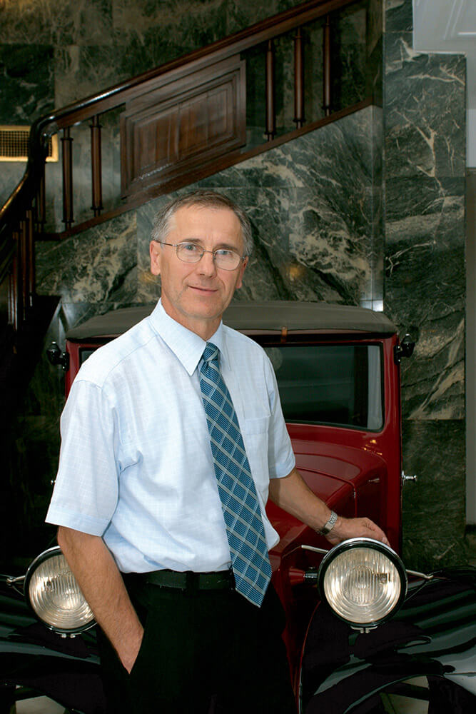 male business portrait by the parked veteran car in interior