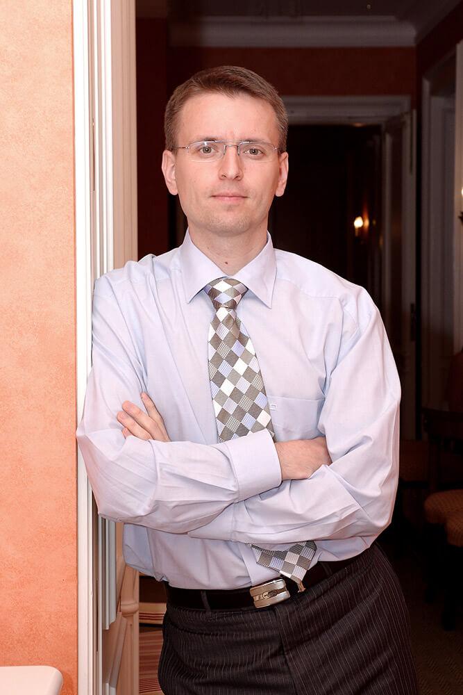 mužský business portrét v košili s kravatou u stěny v interiéru