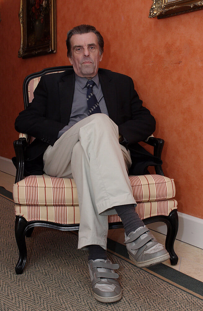 male business portrait in a jacket sitting in an armchair